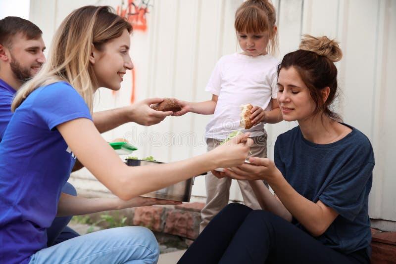 Poor people receiving food from volunteers royalty free stock photos