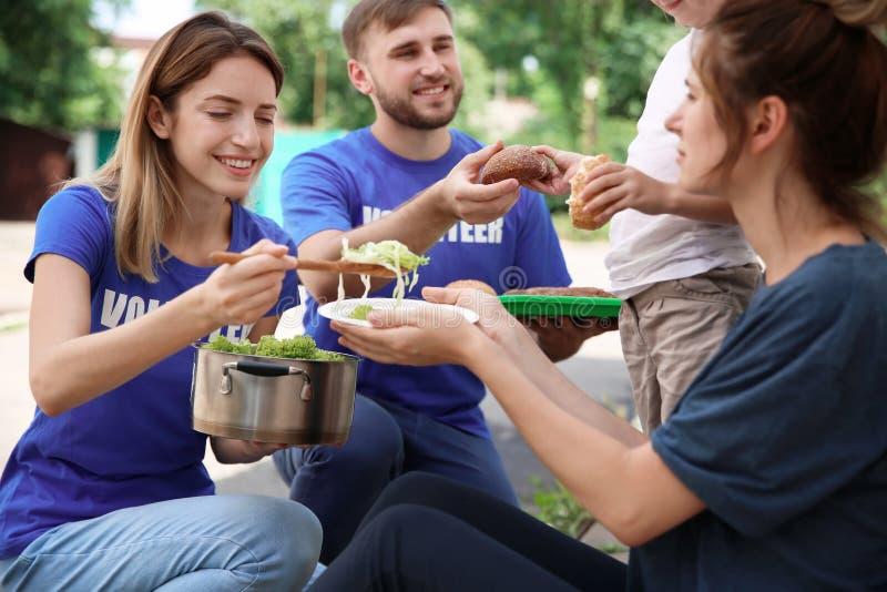 Poor people receiving food from volunteers. Outdoors royalty free stock image