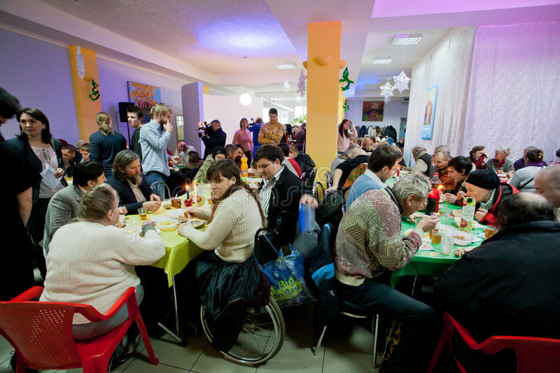 Poor people sit around tables with food at the Christmas charity dinner for the homeless royalty free stock photo