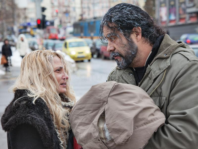 Poor People Winter Cold. Couple of freezing poor homeless people in the winter cold outdoors royalty free stock photography
