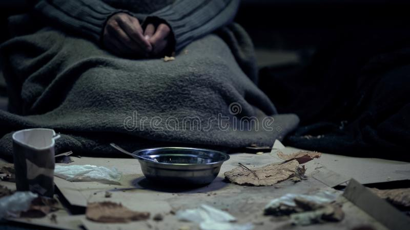 Poor person in dirty cloth sitting front of bowl, living on street, homelessness. Stock photo royalty free stock images