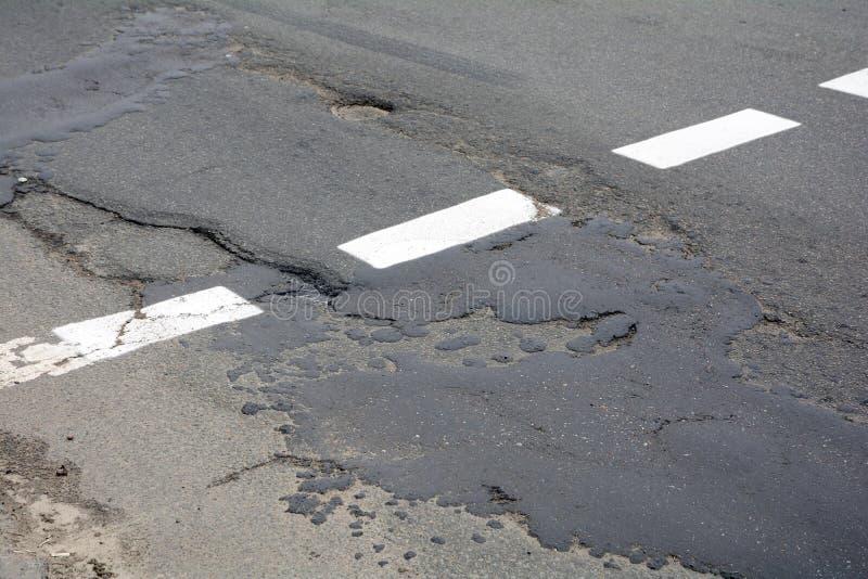 Poor quality of road repair work. Damaged asphalt road, bad road. Poor quality of road repair work. Damaged asphalt road, bad road stock image