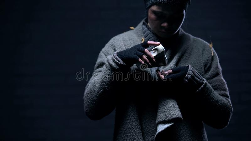 Poor refugee counting coins from paper cup, beggar living on street, donation royalty free stock photos
