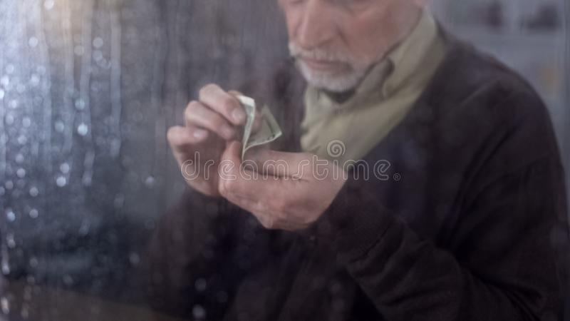 Poor retired man counting money in hand, economic crisis, financial problem stock images
