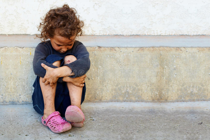 Poor SAD litet barn mot betongväggen arkivbilder