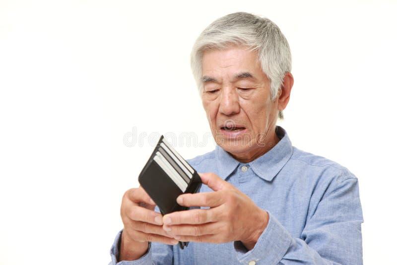 Poor senior Japanese man. Studio shot of senior Japanese man on white background stock photo
