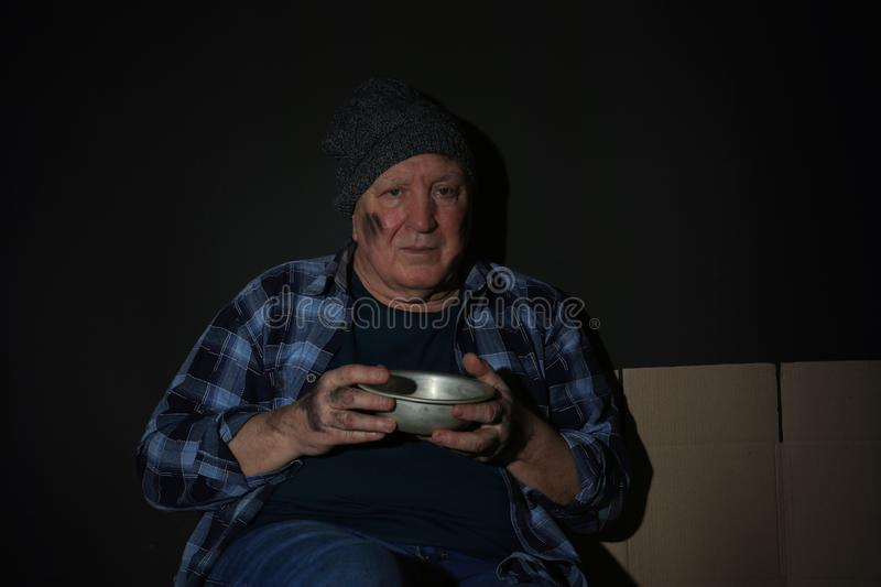 Poor senior man with bowl on dark stock photos