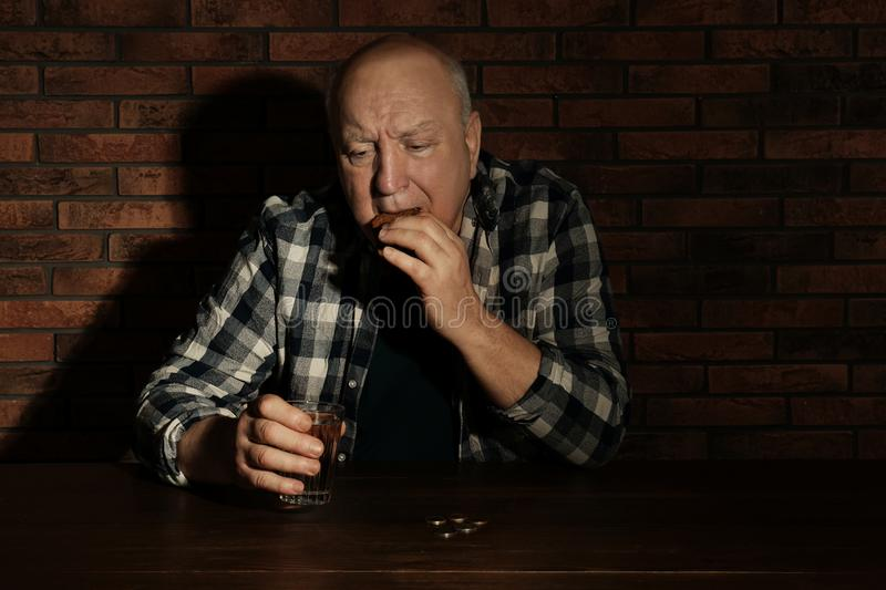 Poor senior man with bread and glass of water at table stock photography