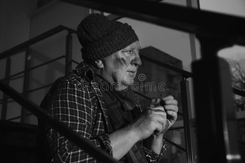 Poor senior man with bread on stairs. Black and white effect stock image