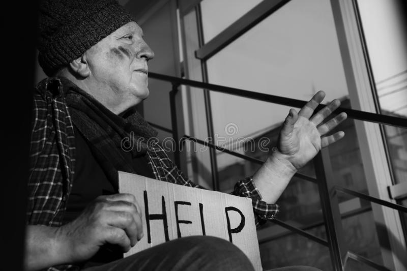 Poor senior man with cardboard sign HELP on stairs. Black and white effect stock photography