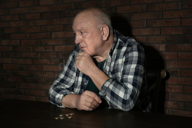 Poor senior man with coins at table stock photography
