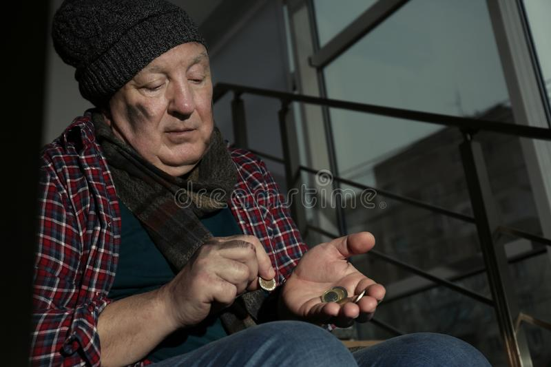 Poor senior man counting coins on stairs indoors royalty free stock photography