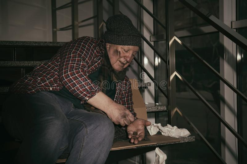Poor senior man counting coins on stairs stock photography