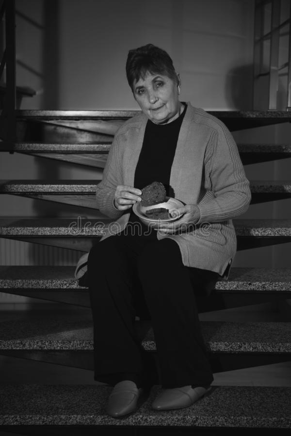 Poor senior woman with bread sitting on stairs, black and white effect stock images