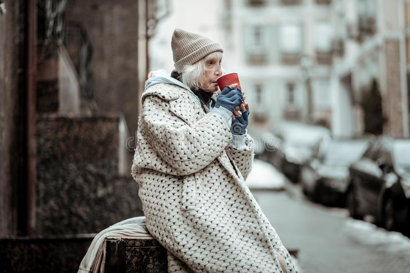 Poor senior woman drinking tea on the street stock photography