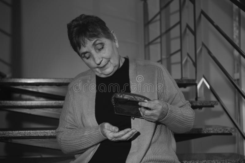 Poor senior woman with empty wallet sitting on stairs. Black and white effect royalty free stock photography