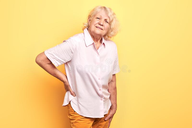 Poor senior woman has back pain. Beautiful old woman touching her back, looking at camera. health problem, health care. isolated yellow background royalty free stock image
