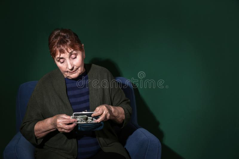 Poor senior woman with money on color background. royalty free stock photo