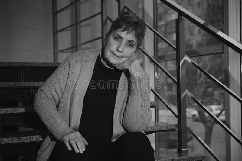 Poor senior woman sitting on stairs. Black and white effect royalty free stock photography