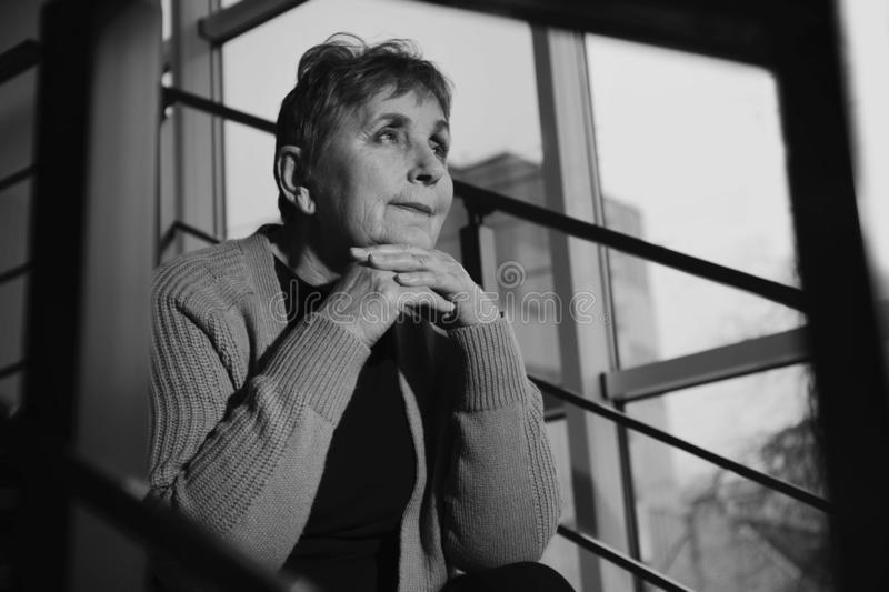 Poor senior woman sitting on stairs. Black and white effect stock photo