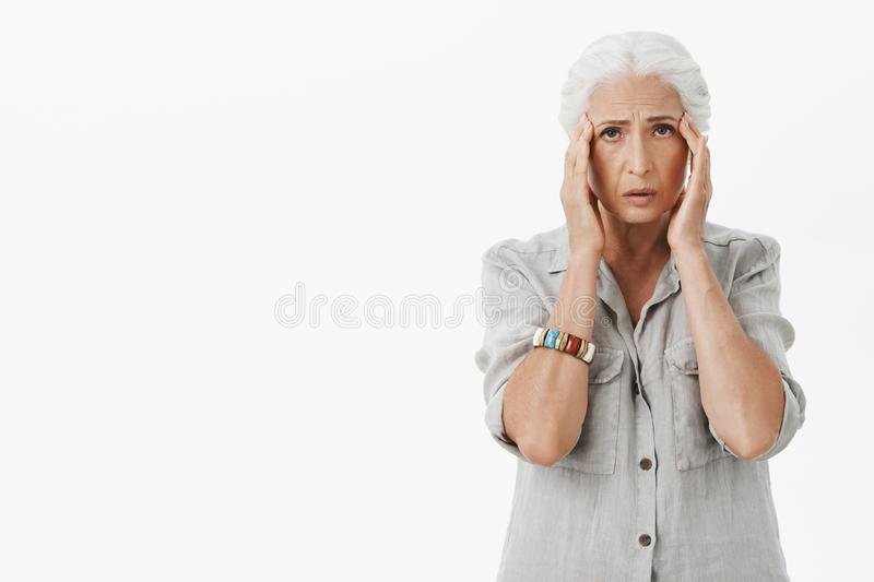 Poor senior woman suffering migraine. Troubled gloomy granny with grey hair holding hands on temples looking sad at stock images