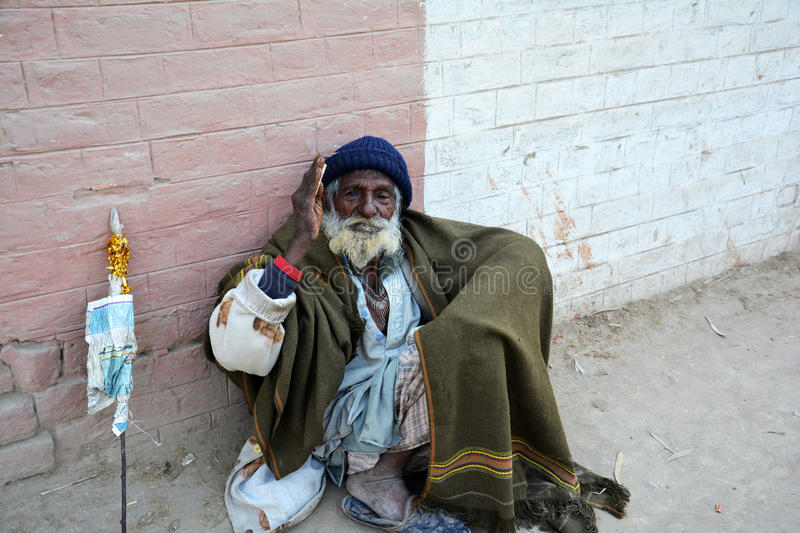 A poor street beggar in Pakistan. A poor, old, homeless street beggar in Pakistan holding 20 Rupees in his hand royalty free stock images