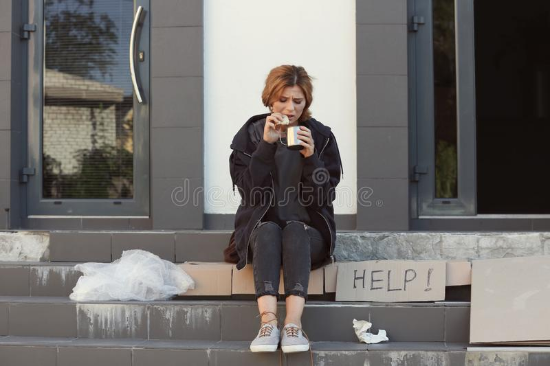 Poor woman with piece of bread and mug royalty free stock photo