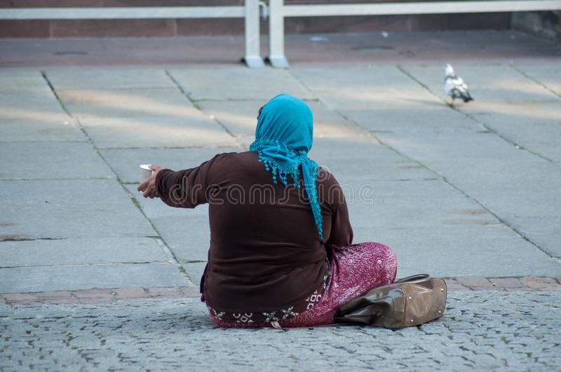 Poor woman  with plastic cup in hands sitting in the street. Portrait of poor woman  with plastic cup in hands sitting in the street stock photography
