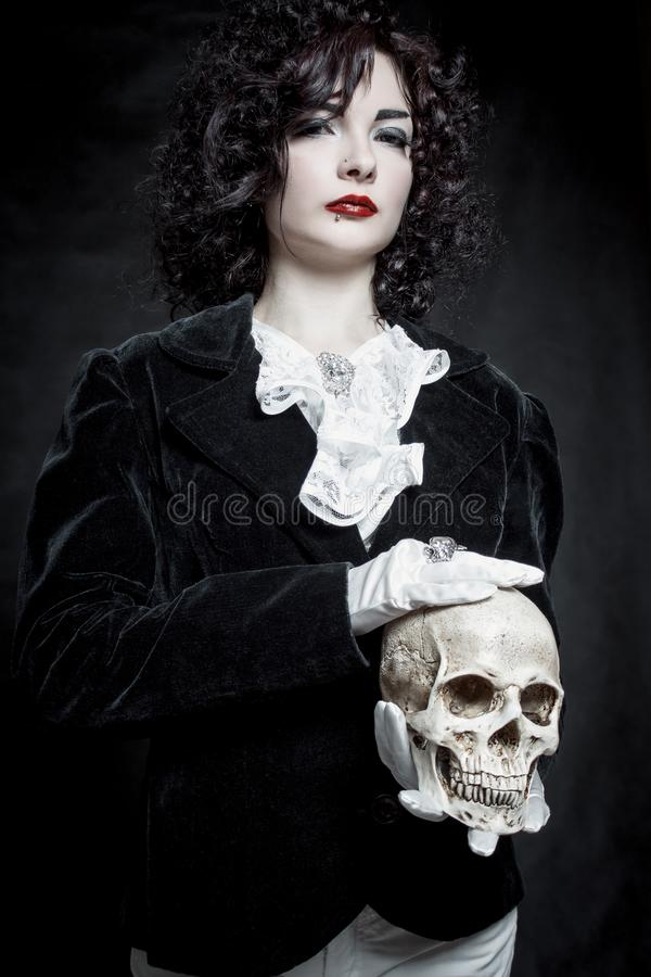 Poor Yorick. Pretty old-fashioned girl posing with skull over dark background stock images
