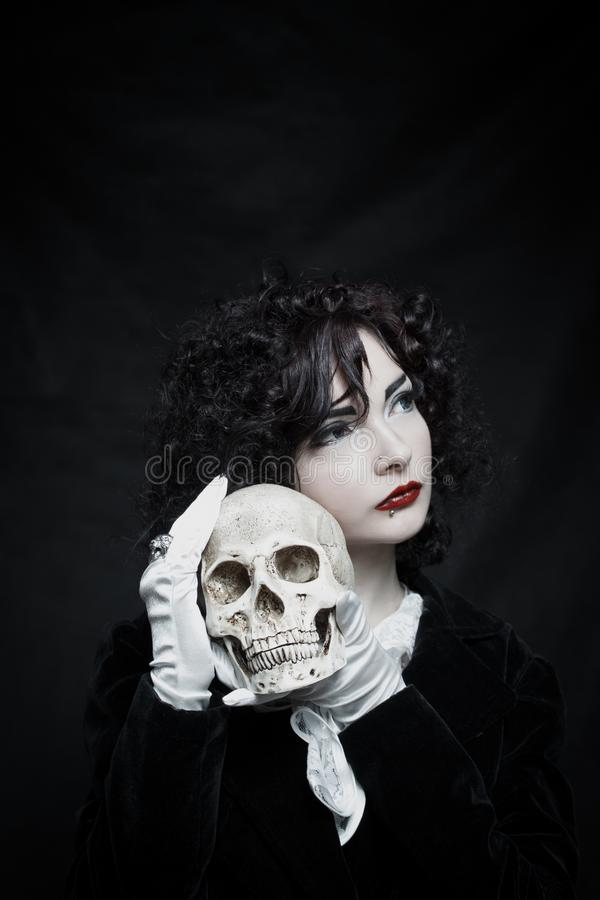 Poor Yorik. Pretty old-fashioned girl posing with skull over dark background royalty free stock photos