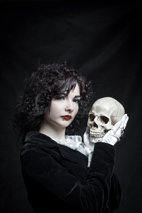 Poor Yorik. Pretty old-fashioned girl posing with skull over dark background stock images