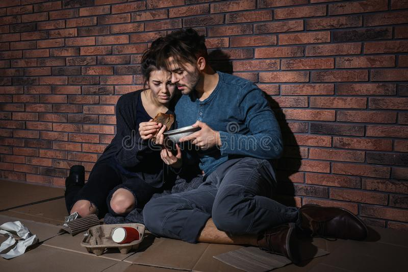 Poor young couple with bread on floor near wall stock photography