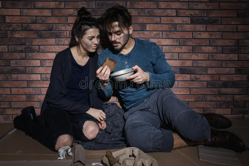 Poor young couple with bread on floor stock photo