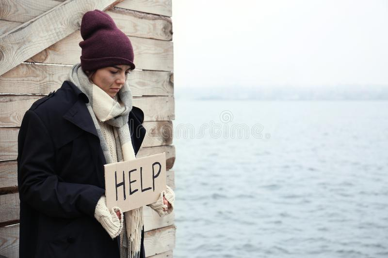 Poor young woman with HELP sign at riverside stock photography