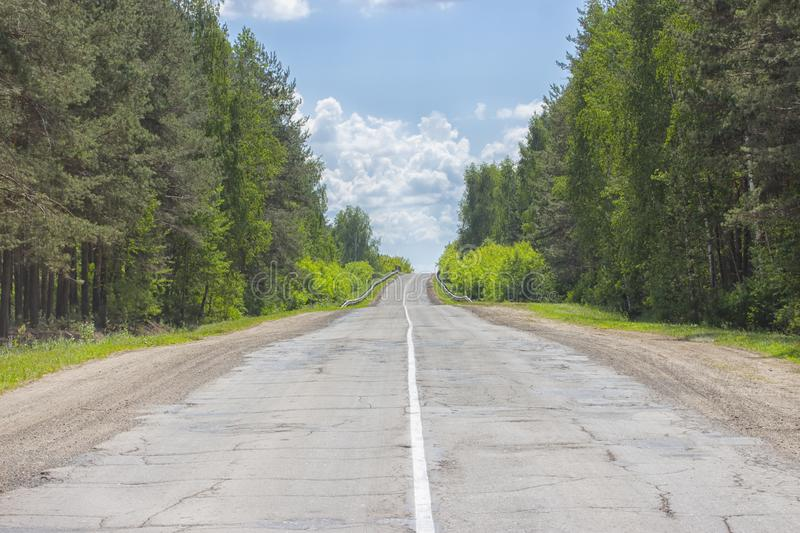A poorly-paved rural two-lane road, deciduous forest, cloudy sky, highway to the horizon stock images