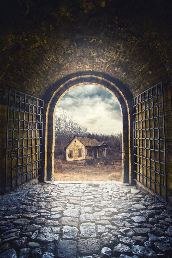Poort die voor weg openen die tot een oud verlaten huis leiden stock afbeelding