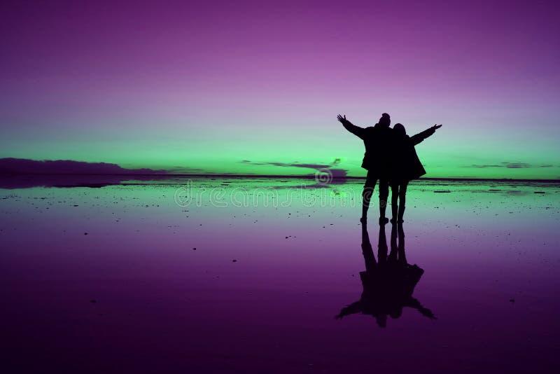 Pop-Art angeredetes Schattenbild von den Paaren, die Arme während des glücklichen Momentes auf Uyuni-Salz-Ebenen, Bolivien anhebe stockbild