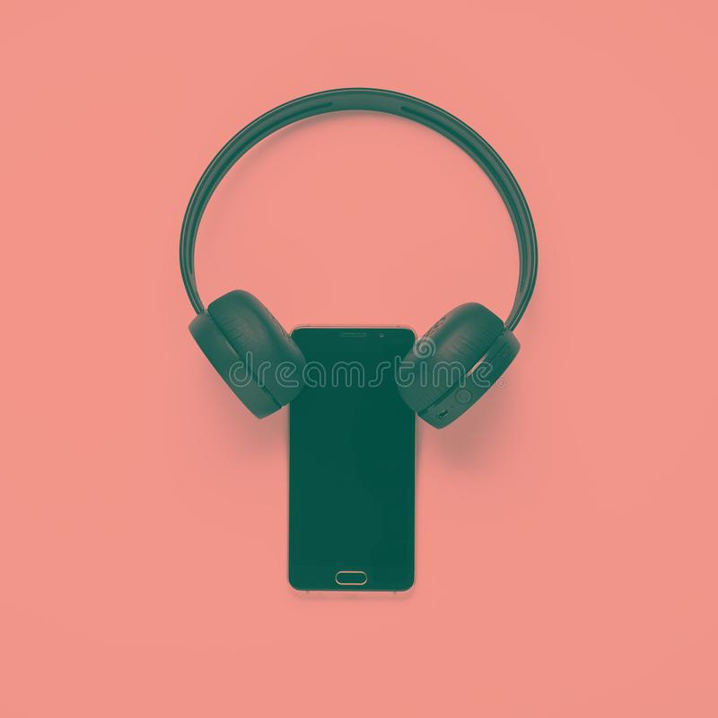 Pop art duotone effect. flat lay smartphone with wireless headphones.  royalty free stock photos