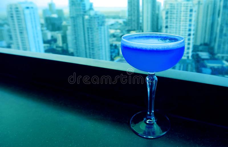 Pop art style royal blue colored cocktail with light blue skyscrapers aerial view in background stock images