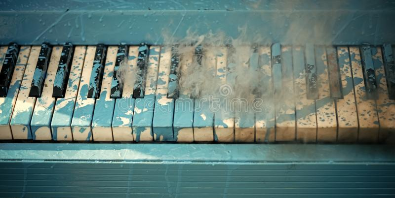 Pop and classical music, melody, rhapsody. Piano in blue paint stain, keyboard. Art, decoration, design, old piano. Painted piano, musical style, grunge stock photography