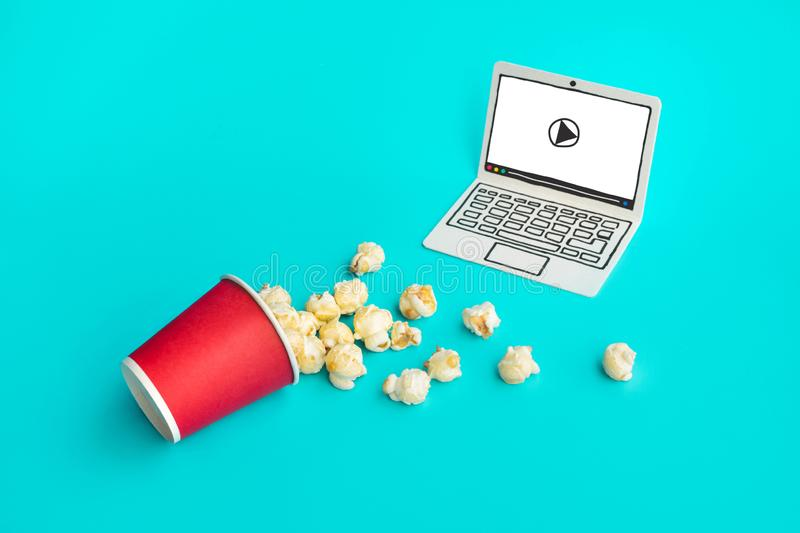 Pop corn with paper art laptop on pastel color background.Food and snack,live stream entertainment.concepts ideas royalty free stock images