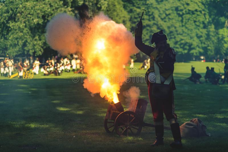Pop off moment of a historical cannon. Popping off a historical cannon during battle reconstruction in a park stock photography
