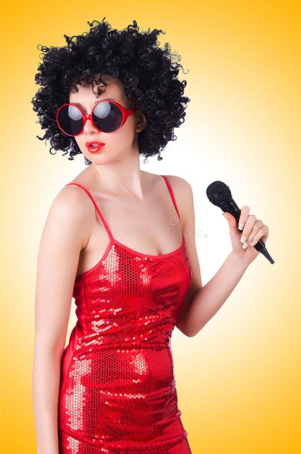 Pop star con il mic in vestito rosso fotografia stock