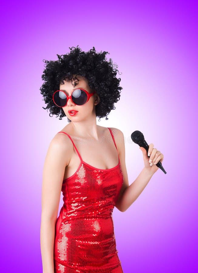 Pop star con il mic in vestito rosso contro immagini stock