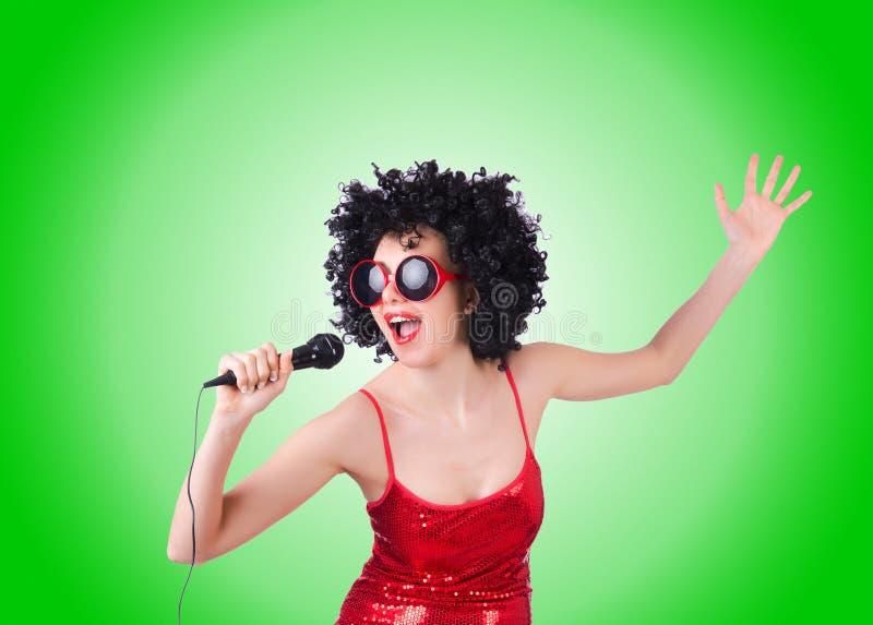 Pop star con il mic in vestito rosso contro la pendenza immagini stock libere da diritti