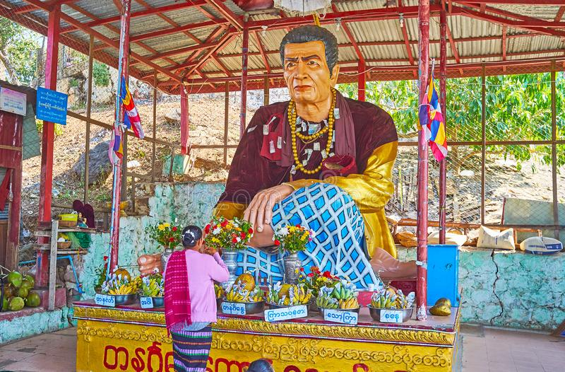 The Nat statue in shrine , Popa, Myanmar. POPA, MYANMAR - FEBRUARY 26, 2018: The Buddhist devotee is making donation at the altar of Nat Spirit deity in covered stock image