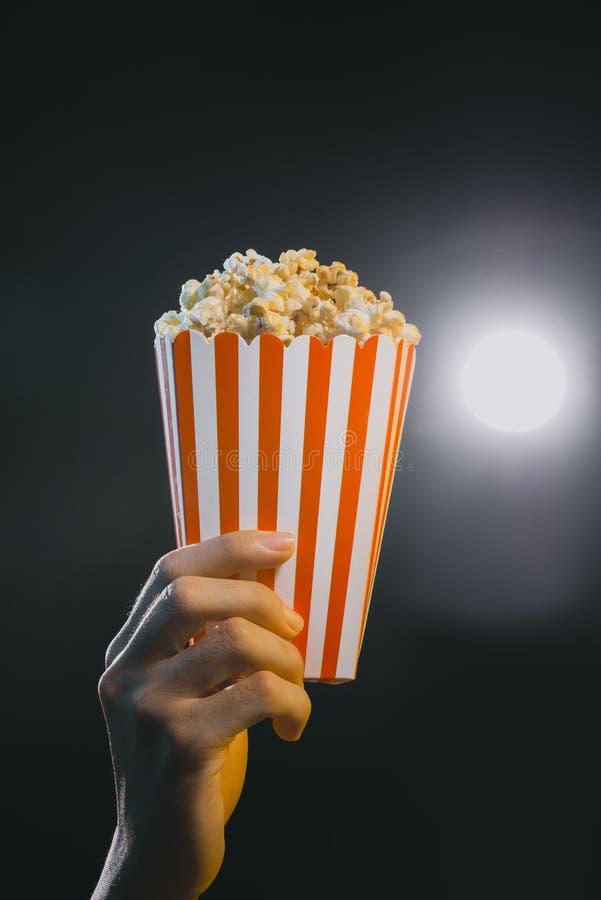 Popcorn εκμετάλλευσης χεριών στο ριγωτό κάδο που απομονώνεται στον κινηματογράφο στοκ φωτογραφία με δικαίωμα ελεύθερης χρήσης