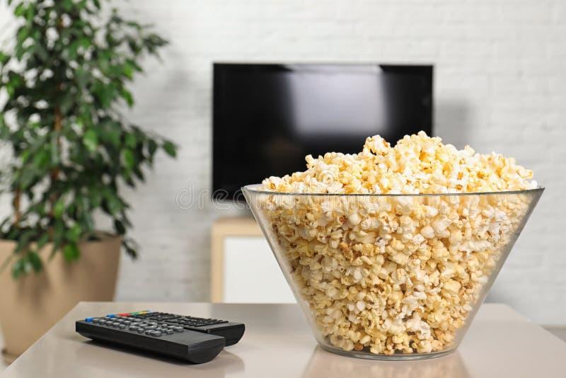 Popcorn και τηλεχειρισμοί TV σχετικά με τον πίνακα στοκ φωτογραφία