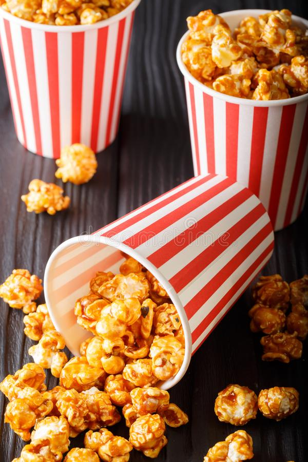 Popcorn καραμέλας στη ριγωτή κινηματογράφηση σε πρώτο πλάνο κιβωτίων στον ξύλινο πίνακα Vertica στοκ φωτογραφία με δικαίωμα ελεύθερης χρήσης