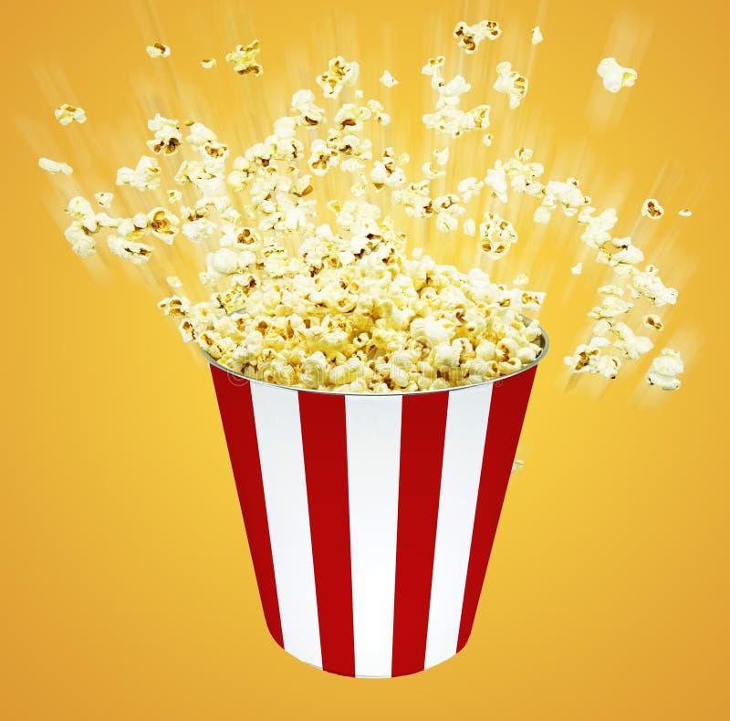 Popcorn πλάγιας όψης στο ριγωτό κίτρινο backgrou κάδων explosionon στοκ φωτογραφία με δικαίωμα ελεύθερης χρήσης
